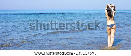 Gorgeous woman walking with hat in deep blue ocean/Fantastic beautifufl woman standing in the ocean