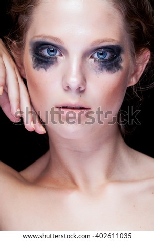 Gorgeous woman with black crying make up and blue eyes