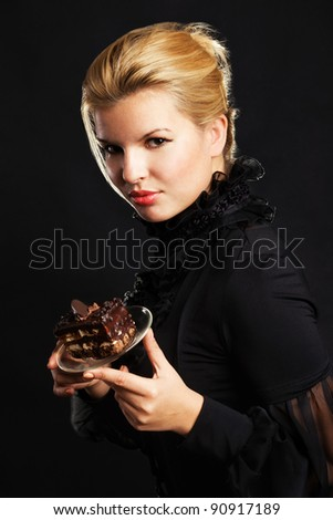 Gorgeous woman with chocolate cake against black - stock photo