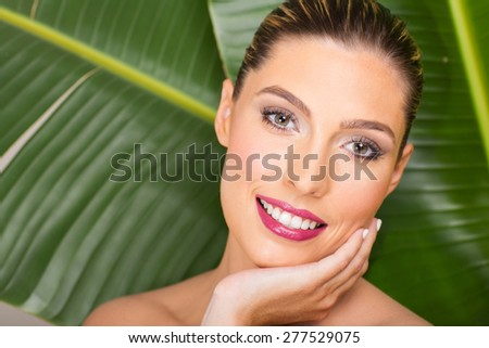 gorgeous woman with clean makeup over green leaf - stock photo