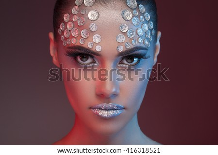 Gorgeous woman with fashion rhinestone make up on blue and red toning image in studio