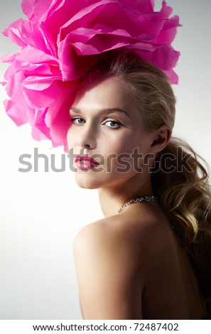Gorgeous woman with pink flower on head looking at camera - stock photo