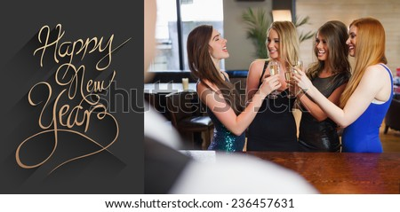 Gorgeous women clinking their flutes of champagne against classy new year greeting - stock photo