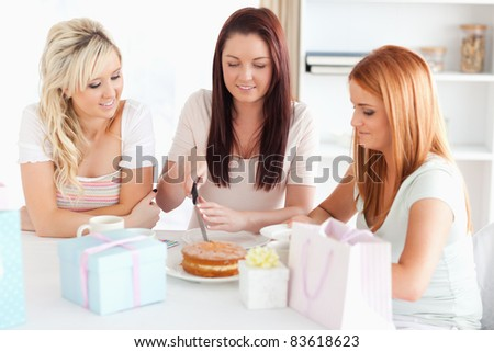 Gorgeous Women sitting at a table cutting a cake in a kitchen