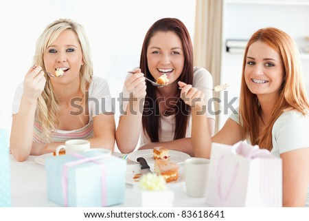Gorgeous Women sitting at a table eating a cake in a kitchen