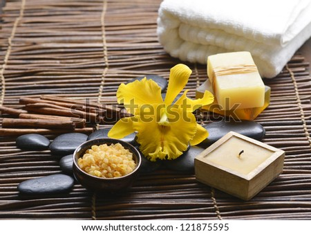 gorgeous yellow orchid with stones ,candle, salt in bowl on mat background
