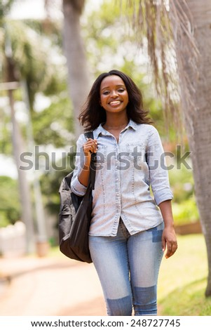 gorgeous young african college student walking on campus - stock photo