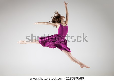 Gorgeous young ballet dancer wearing purple dress over grey background - stock photo