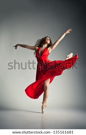 Gorgeous young ballet dancer wearing red dress over dark grey background - stock photo