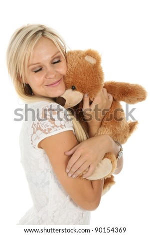 Gorgeous young blond woman hugging a stuffed bear toy - stock photo