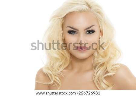 Gorgeous young blond woman with dark eye makeup and long curly hair posing with bare shoulders facing the camera with a smile, isolated on white
