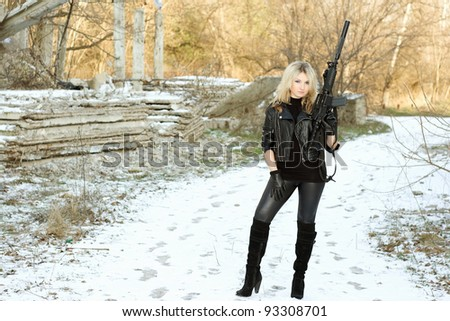 Gorgeous young blonde with a gun outdoors - stock photo