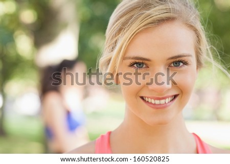 Gorgeous young blonde woman posing in a park smiling at camera