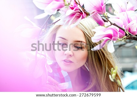 Gorgeous young blonde woman with blue eyes posing near blooming pink flowers. Spring time - stock photo