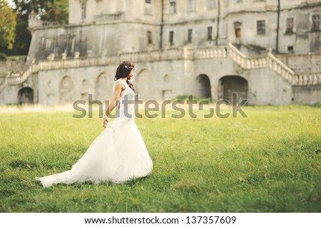 gorgeous young bride walking next to castle in west Ukraine - stock photo