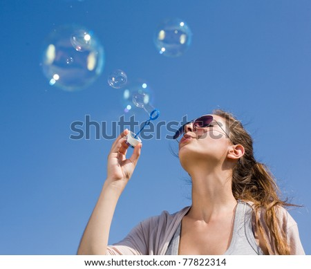 Gorgeous young brunette blowing soap bubbles into the sky.