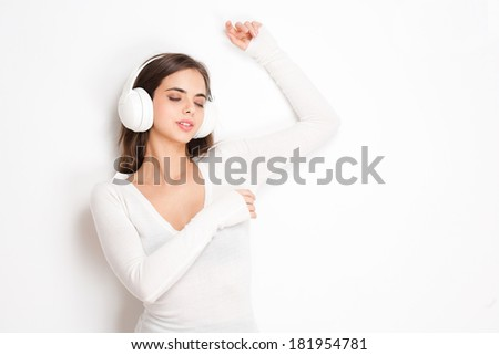 Gorgeous young brunette enjoying music in white headphones. - stock photo
