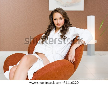 Gorgeous young brunette girl relaxing after spa in white bathing robe, in luxurious environment. - stock photo