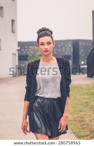 Gorgeous young brunette in black skirt posing in an urban context - stock photo