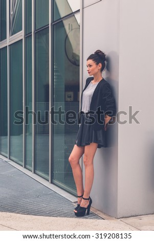 Gorgeous young brunette in black skirt posing in an urban context