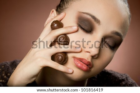 Gorgeous young brunette in dark makeup with chocolate. - stock photo