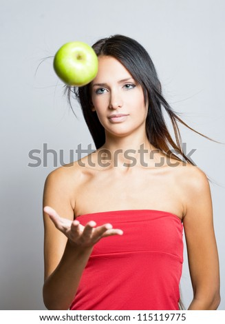 Gorgeous young brunette juggling green apple. - stock photo