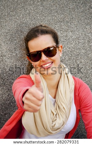 Gorgeous young brunette showing big thumbs up on urban location. - stock photo