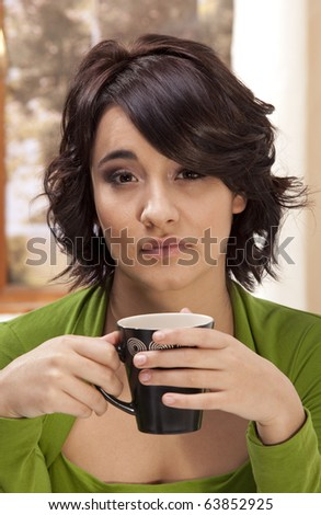Gorgeous young brunette with a cup of coffee, with a somber expression on her face. - stock photo