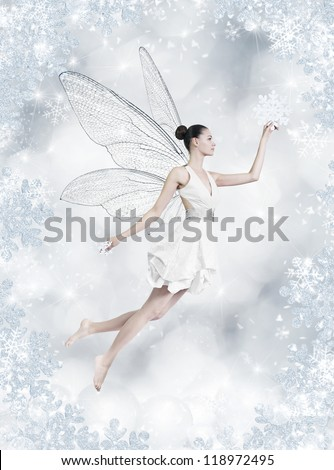 Gorgeous young brunette woman as winter fairy with wings on shiny silver background - stock photo