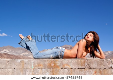 Gorgeous young brunette woman sun tanning on a concrete wall - stock photo