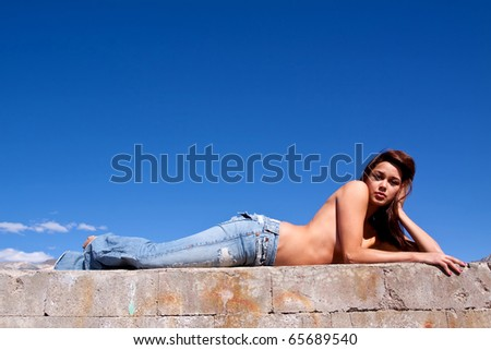 Gorgeous young brunette woman sun tanning on a concrete wall