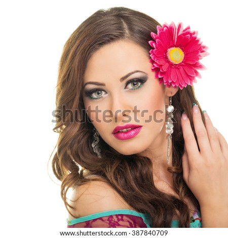 Gorgeous young brunette woman with pink flower in her hair. Gorgeous green eyed Caucasian female model posing, wearing makeup and earrings. Retouched, isolated on white background. - stock photo