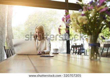 Gorgeous young business woman having cell phone conversation while sitting front open laptop computer in modern coffee shop interior, female person talk on smart phone while looking to net-book screen - stock photo