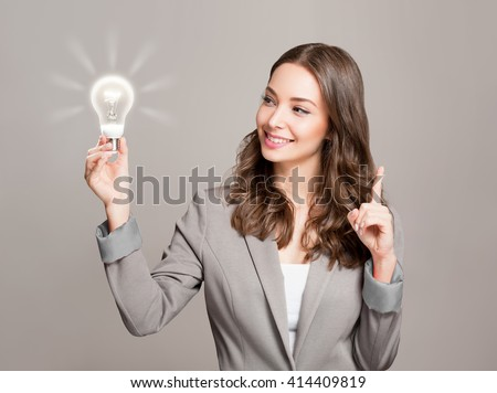 Gorgeous young businesswoman holding glowing light bulb idea symbol. - stock photo