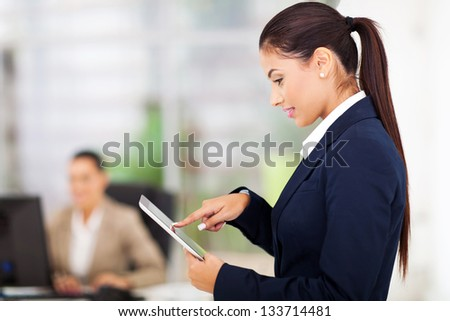 gorgeous young businesswoman using tablet computer in office - stock photo