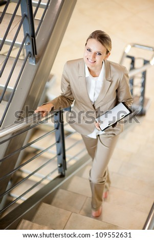 gorgeous young businesswoman walking up stairs - stock photo