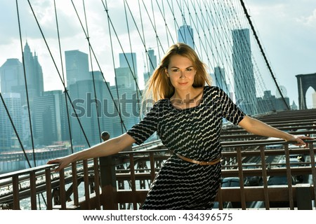 Gorgeous Young Caucasian blonde woman in fashionable clothes posing outdoors at the Brooklyn Bridge, New York City. - stock photo