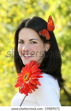 Gorgeous young Caucasian woman outdoors, in a park, with a bright red flower and a red butterfly - stock photo