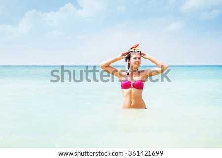 Gorgeous, young lady in pink swimwear with snorkeling mask swimming in the sea and ready to dive. - stock photo