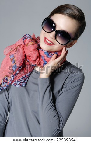 gorgeous young lady in sunglasses with scarf on gray background - stock photo