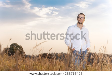 Gorgeous young man standing in a grass wearing white shirt, outdoors. Guy in nature, copyspace for text - stock photo