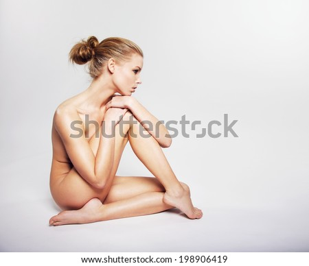 Gorgeous young nude woman sitting on the floor. Caucasian female model covering her body with her leg looking away at copy space on grey background - stock photo