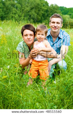 Gorgeous young parents and sweet toddler in grass - stock photo