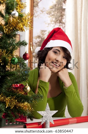 Gorgeous young smiling woman sitting with her fists under her chin next to a Christmas tree in her home, wearing a Santa Clause hat. - stock photo