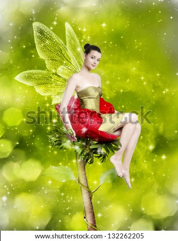 Gorgeous young woman as spring fairy sitting on red flower on green background - stock photo