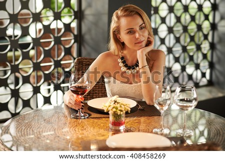Gorgeous young woman drinking red wine alone in restaurant - stock photo