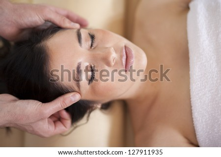 Gorgeous young woman getting a head massage at a spa