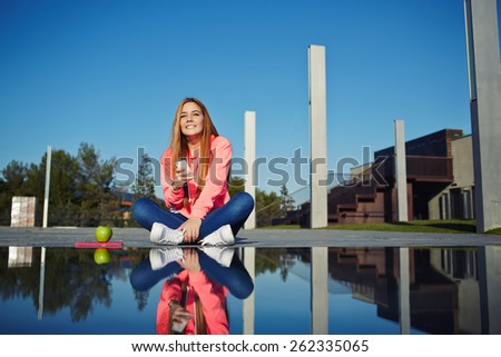 Gorgeous young woman holding her smart phone sitting at beautiful park on sunny day, attractive girl sitting next to the water with amazing reflection of her self, female student using cell phone - stock photo