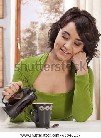 Gorgeous young woman in her home, pouring herself a cup of coffee from a french plunger. - stock photo