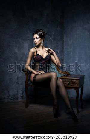 Gorgeous young woman in sexy lingerie and stockings posing in a vintage interior.
